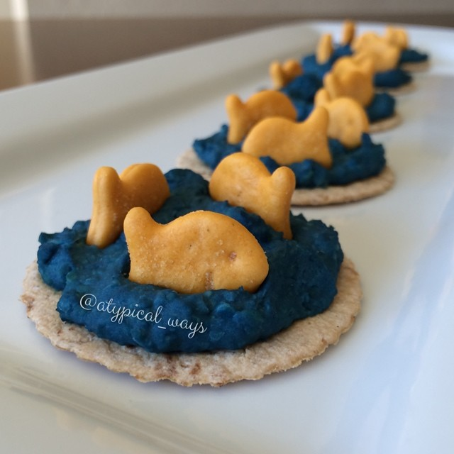 Goldfish & blue Nacho Cheese Hummus on baked pita rounds....because you can pretty much trick kids into eating anything if it looks cool